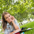 Young smiling student lying on grass on phone — Stok Fotoğraf #38458853