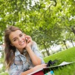 Young smiling student lying on grass on phone — Stock Photo #38458853