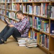 Smiling young student sitting on library floor using tablet — Stockfoto #38459647