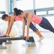 Two women performing step aerobics exercise in gym — Stock Photo #38459725
