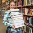 Cheerful student holding heavy pile of books standing in library — Stock Photo