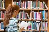 Zrzka student čtení knih z police v knihovně — Stock fotografie
