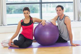 Young woman and man with fitness ball sitting at gym — Stock Photo