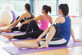 Class doing the half spinal twist pose on mats at yoga class — Stock Photo