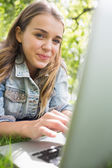 Young smiling student lying on the grass using her laptop — Stock Photo