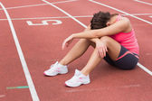 Tensed sporty woman sitting on the running track — Stock Photo