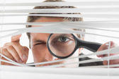 Businessman peeking through blinds with magnifying glass — Stock Photo