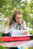 Pretty student lying on the grass studying with her tablet pc — Stock Photo