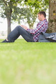 Student using his laptop to study outside — Stock Photo