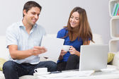 Smiling couple paying their bills online at home — Stock Photo
