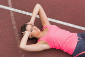 Sporty woman suffering from headache on the running track — Stock Photo