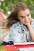 Smiling young student studying on grass — Stock Photo