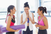 Three fit young women smiling in exercise room — Stock Photo