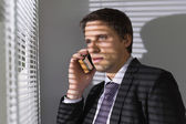 Businessman peeking through blinds while on call in office — Stock Photo