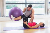 Trainer helping young woman with fitness ball at gym — Stock Photo