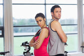 Serious young woman and man standing back to back in gym — Stock fotografie