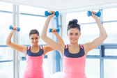 Two women performing step aerobics exercise with dumbbells — Stock Photo