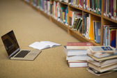 Laptop and books on the floor of library — Stock Photo