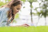 快乐的学生躺在草地使用她的笔记本电脑上 — 图库照片