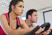 Young man and woman working out at spinning class — Stok fotoğraf