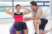 Trainer helping woman do abdominal crunches on fitness ball — Stock Photo