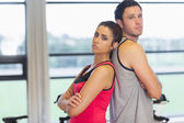 Serious young woman and man standing back to back in gym — Stok fotoğraf