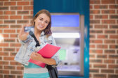 Pretty student standing showing her card to camera at the atm — Stock Photo