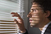 Serious businessman peeking through blinds in office — Stock Photo