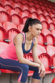 Smiling toned woman sitting on chair in the stadium — Stock Photo