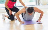 Female trainer assisting man with push ups in gym — Stock Photo