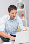 Serious man using laptop at home — Stock Photo