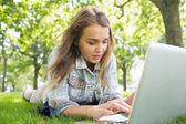 年轻漂亮的学生躺在草地使用的便携式计算机上 — 图库照片