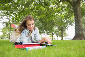 Happy student lying on the grass studying — Stock Photo