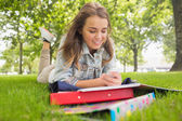 Pretty smiling student lying on the grass sending a text — Fotografia Stock
