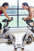 Side view of a woman and man working out at spinning class — Stock Photo