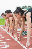 Young people ready to race on track field — Stock Photo