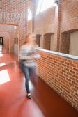 Young student rushing in the hall holding folders — Stock Photo