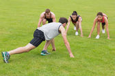Young people doing stretching exercise at the park — Stock Photo