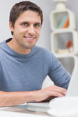 Smiling young man using laptop in living room — Stock Photo