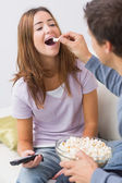 Cropped man feeding popcorn to a happy woman at home — Stock Photo