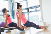 Two fit women performing step aerobics exercise in gym — Stock Photo