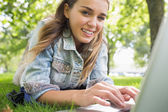 Young smiling student lying on the grass using laptop — Stock Photo