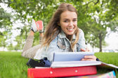 Smiling student lying on the grass studying with her tablet pc — Stock Photo