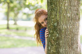 Cute redhead hiding behind a tree — Stock Photo