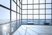Room with large window showing city — Stock Photo