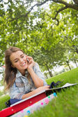 Young happy student lying on the grass on the phone — Stock Photo
