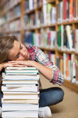 Napping student sitting on library floor leaning on pile of books — Stock Photo