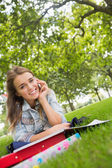 Young smiling student lying on the grass on the phone — Stock Photo
