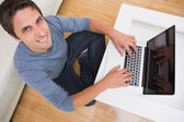 Overhead portrait of a man using laptop in living room — Stock Photo