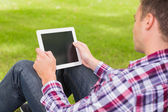 Happy student using his tablet outside — Stock Photo